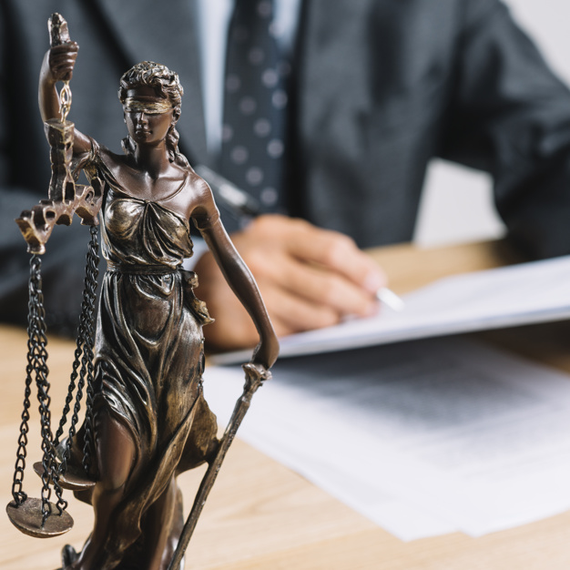 close-up-themis-lady-justice-holding-scale-front-lawyer-working-desk_23-2147898349